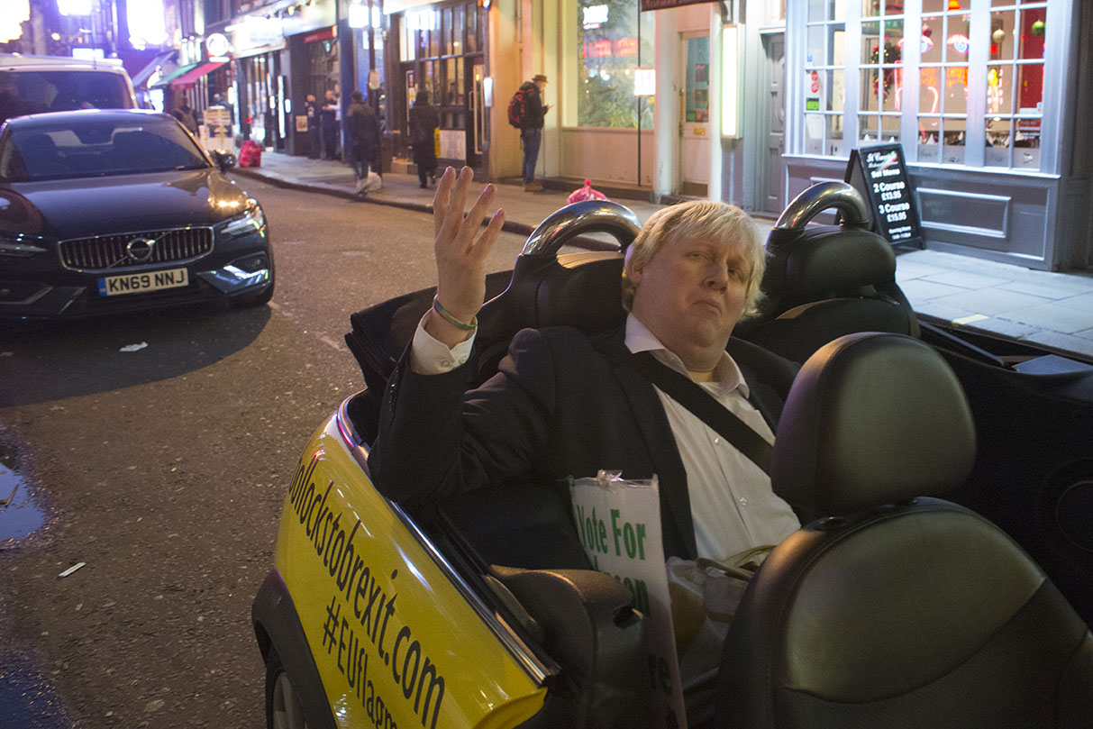 3 Dec 2019 - London, UK - Faux Bojo (Drew Galdron) in mini at Old Compton Street in a stunt organised and crowdfunded by anti-brexit campaigning group EU Flag Mafia.