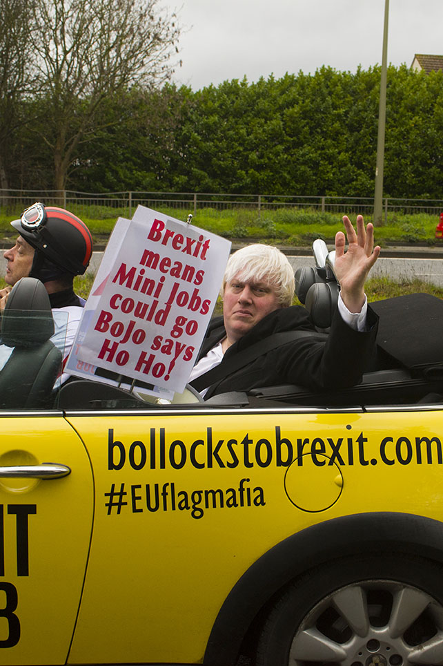Oxford, UK - 06 Dec 2019 - EU Flag Mafia minis visit Oxford (the Cowley Mini Factory), to protest against Brexit and call for a tactical vote. The minis used by the group were built in the UK but have BMW engines highlighting the single market approach to manufacture. This is under threat with Brexit. EU Flag Mafia are an anti-brexit protest group. Boris Johnson impersonater Drew Galdron in shot.